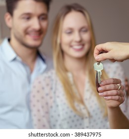 Estate agent handing over a set of keys to a new home or rental accommodation to a smiling young couple, focus to the keys