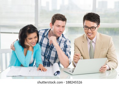Estate agent presenting a house to the young couple by using a laptop