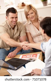 Estate agent shaking hand with young man, making deal with smiling couple in new house.?