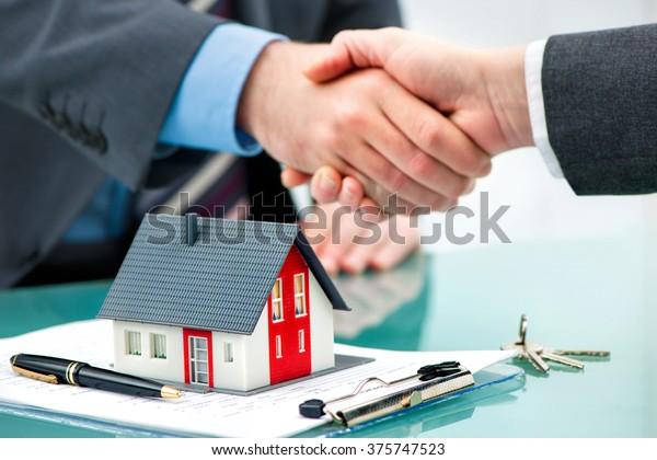 Estate-Agent schüttelt dem Kunden nach Vertragsunterzeichnung die Hand