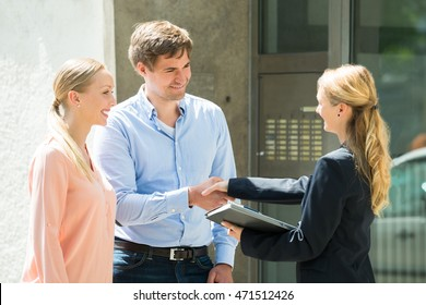 Estate Agent Shaking Hands With Happy Young Couple After Buying House