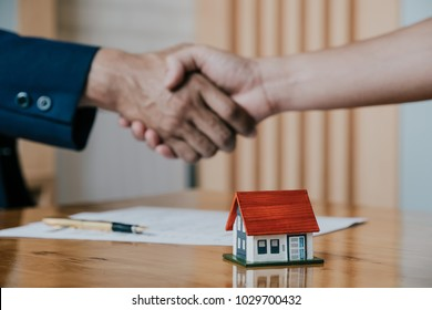 Estate agent shaking hands with his customer after contract signature, Contract document and house model on wooden desk