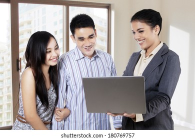 Estate agent showing her project on laptop to young couple