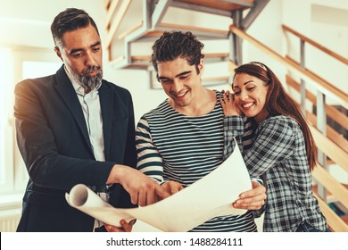 Estate agent is showing house to couple buyers, telling clients about home advantages. Interior designer is discussing renovation ideas with homeowners.
