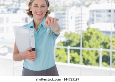 Estate agent showing house keys and smiling at camera in a bright office