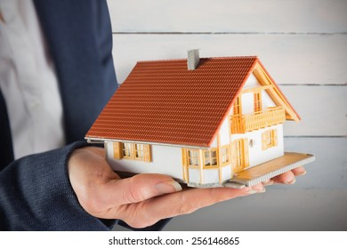 Estate agent showing mini house against painted blue wooden planks