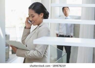Estate agent talking on phone with buyer in background in empty house