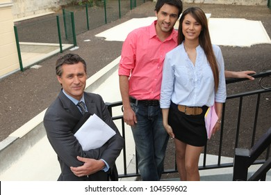 Estate agent and young couple stood outside property