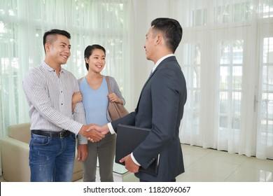 Estate broker shaking hands of customer after confirming deal