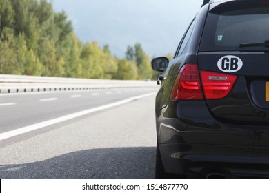 Estate vehicle parked up on a autostrada/highway/motorway showing the road disappearing. The car has a GB country of origin sticker, with the background in blur. showing the car in focus.