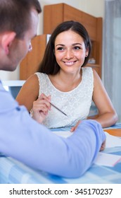 Estate young agent explaining offer to client and smiling in office