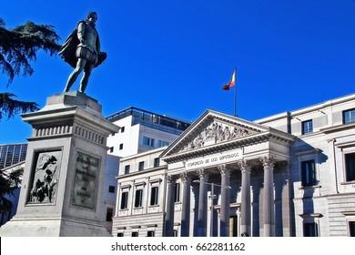 Estatua de Cervantes y la capsula del tiempo, the figure represents the writer in his time suit, with Congress of Deputies of Spain (Congreso de los Diputados) on Plaza de las Cortes, Madrid, Spain