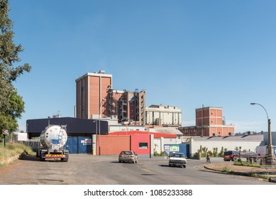ESTCOURT, SOUTH AFRICA - MARCH 21, 2018: Street scene in Estcourt with the factory of the Nestle company, milk truck and cars visible