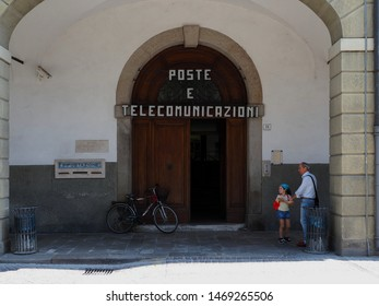 Este, Italy - July 17, 2019. Post office with bicycle, grandfather and granddaughter smile happily.
