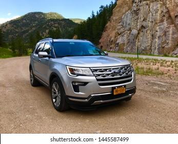 Estes Park, Colorado. July 1, 2019. A Ford Explorer parked by rocks and hills of Colorado near Estes Park.