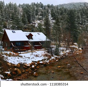 Estes Park, Colorado / United States - April 25, 2018:  Snow scene featuring cabin nestled in Rocky Mountains near running river