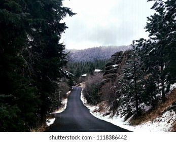 Estes Park, Colorado / United States - April 25, 2018:  Road to Estes Park, Colorado with evergreen forest, snow with mountains and clouds in the distance
