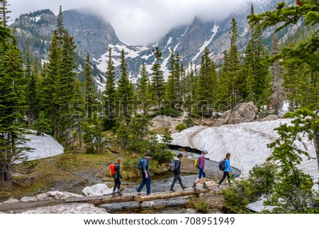 Estes Park, Colorado, USA - June 24, 2017: On a foggy spring day, a group of hikers walking cross a tree trunk bridge over Tyndall Creek on Emerald Lake Trail at base of Hallett Peak and Flattop Mtn.