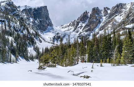 Estes Park, Colorado, USA - May 24, 2019: Lakes are still frozen. A few brave visitors hiking along snow-covered Dream Lake towards Hallett Peak and Flattop Mountain in Rocky Mountain National Park.