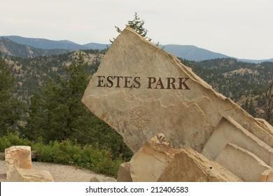 ESTES PARK, COLORADO/U.S.A. - AUGUST 8, 2013:  The stone entrance sign to the Colorado mountain town of Estes Park, Colorado. The background is pine trees and mountains.