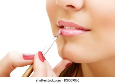 esthetician apply lipstick on female lips closeup, isolated on white background