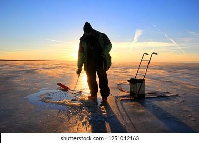 Pärnu, Estonia february 17 2017: lonely Ice fishing anglers on ice in Pärnu bay, Baltic sea, Estonia and yellow sunrise