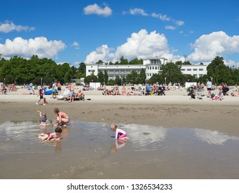 Pärnu, Estonia - July 23, 2017: People relaxing on the long, picturesque beach of the Baltic Sea. Children are swimming in the refreshing sea water.
