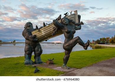 ESTONIA, KURESSAARE, SEPTEMBER 22, 2016: Statues of folk Estonian ?haracters Suur Toll and Piret in Kuressaare. Dawn over Saaremaa island