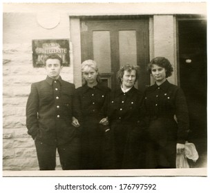 ESTONIA, TALLINN - CIRCA 1930s: An antique photo of Three women and a man in uniform against the backdrop of Railroaders Club on the street Kopli