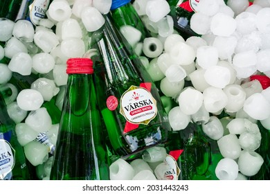 Estonia-07.21.2021: Cold water put on ice. Lots of glass bottles with cold Värska water. Ice cubes around cold water bottles. Estonian produced Värska water in small glass bottles. Refreshments on ice