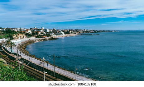 Estoril, Portugal - December 24, 2020: High perspective view of promenade towards Estoril in Portugal. This stretch of coastline is called the Coast of Kings or Green Coast