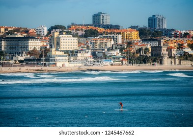 Estoril, Portugal - Nov 30, 2018: Man does stand up paddle overlooking the coast of Estoril near Lisbon, Portugal - with copy space