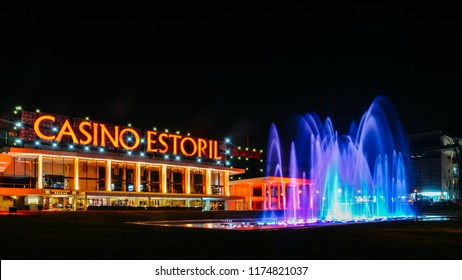 Estoril, Portugal - Sept 8th, 2018: Facade of the Casino Estoril with colourful fountain show at night, one of the largest casinos in Europe and inspiration for Ian Fleming's Casino Royale