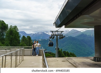 """Estosadok, Sochi, Russia - June 10.2017: Tourists are photographed against the backdrop of the mountains to the cable car station of the ski resort """"Rosa Khutor"""" summer cloudy day"""