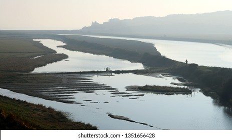 The estuary of the Cuckmere River on England's south coast. Silhouetted are the old coastguard cottages by the sea. This photograph taken on a misty winter's morning.