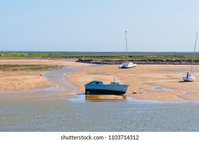 In the estuary at low tide an old motor boat, catamaran and small yacht stand on the sand amidst tidal pools and streams