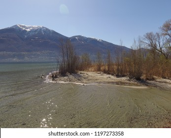 Estuary of Maggia at Lago Maggiore,close to Locarno+Ascona/TI, Switzerland. blue sunny sky, droneflight, early spring, calm + verry clear water, little snow on mountains in the background
