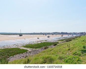 In the estuary at Wells-next-the-Sea pleasure yachts sit beached on the sand at low tide. In the distance is the town and quayside.