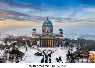 Esztergom, Hungary - Aerial view of the beautiful snowy Basilica of Esztergom with Slovakia at the background on a foggy winter morning