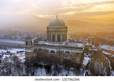 Esztergom, Hungary - Aerial view of the beautiful snowy Basilica of Esztergom on a foggy winter morning with golden sunrise