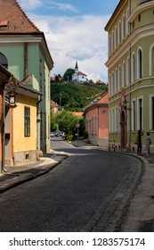 Esztergom Hungary Jun 13 2018: Colorful old buildings, winding streets, church with cross on the hill - these are so typical of Esztergom