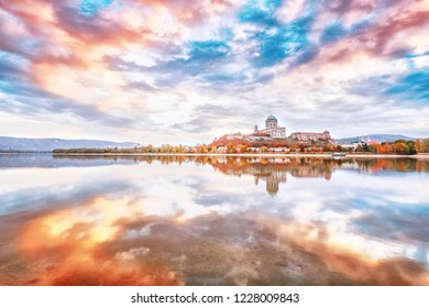Esztergom, Hungary - view over Danube river from Sturovo, Slovakia. Epic sunrise landscape with dramatic sky of famous Basilica Esztergom. Amazing reflections clouds. Orange and blue colors in nature.