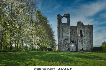 Etal Castle - a ruined medieval fortification in the village of Etal, Northumberland, England. Spring warm day with the blue cloudy sky in the background.