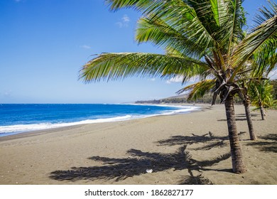 Etang-Sale beach on Reunion Island with its characteristic black sand and the waves of the Indian Ocean