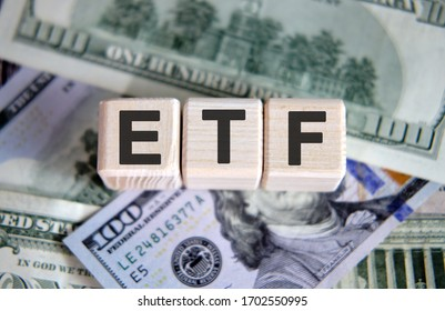 ETF financial business concept. Wooden cubes and paper dollar bills as a background
