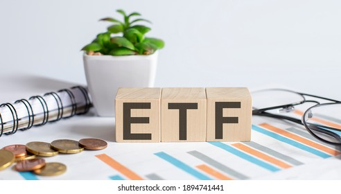 ETF word on wood blocks concept with chart, coins, notebook , glasses.