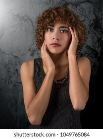 Ethereal beautiful mixed race young woman with amazing eyes and curly hair against a grunge background