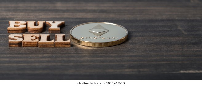 Ethereum coin crypto currency with 'BUY' and 'SELL' text on dark wooden table top