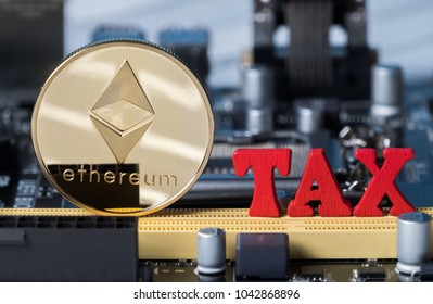 Ethereum coin crypto currency with red 'TAX' word on computer motherboard