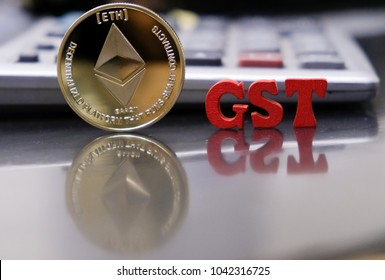 Ethereum coin cryptocurrency with GST text against calculator on a work desk